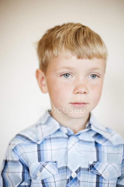 Retrato de menino loiro com sardas contra a parede em casa — Fotografia de Stock