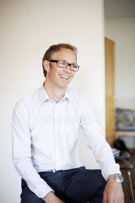 Mature man sitting in front of white wall in home interior — Stock Photo