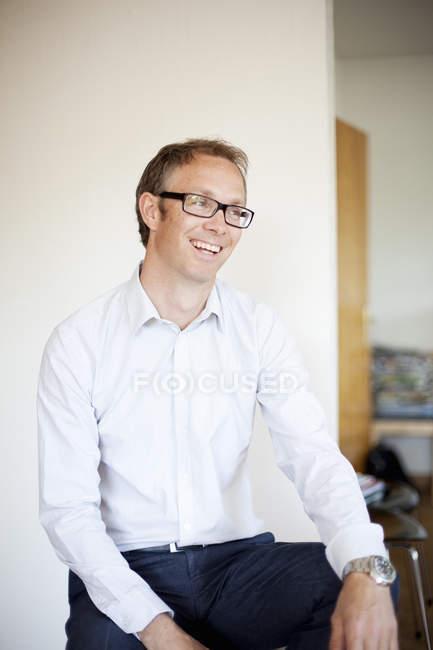 Homme d'âge mûr assis devant un mur blanc à l'intérieur de la maison — Photo de stock