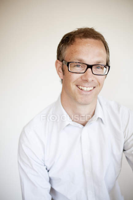 Portrait of mature man against white wall at home — Stock Photo