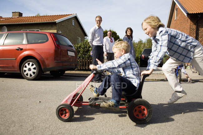 Boy pushing brother on quadricycle with family in background — Stock Photo