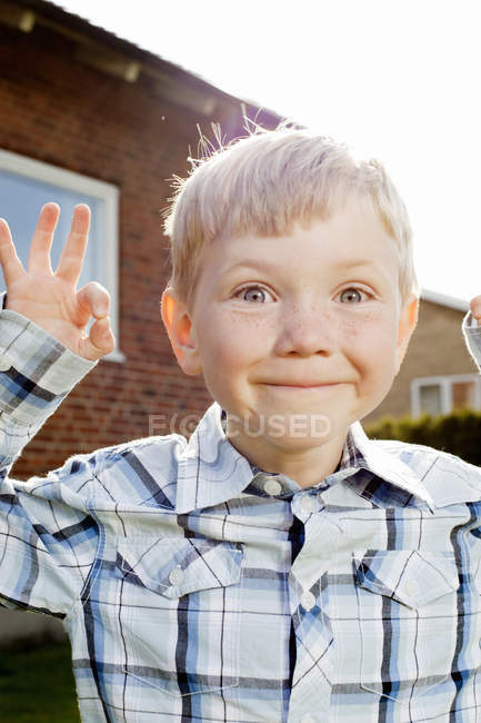 Portrait of boy showing ok sign in back yard and making funny face — Stock Photo