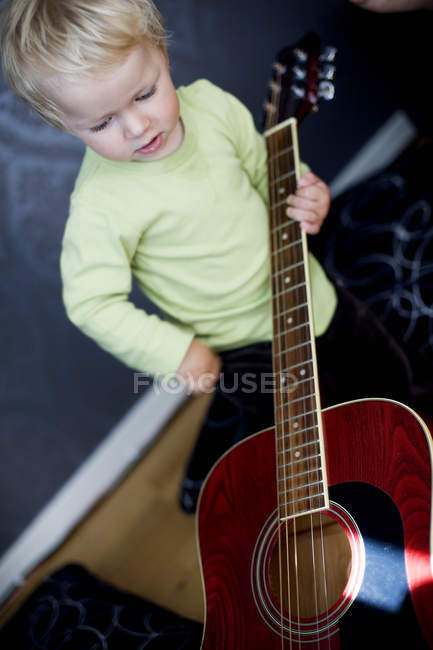 High angle view of boy playing with guitar at home — Stock Photo