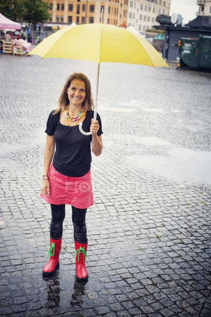 Щасливі жінка під парасолькою жовтий — стокове фото