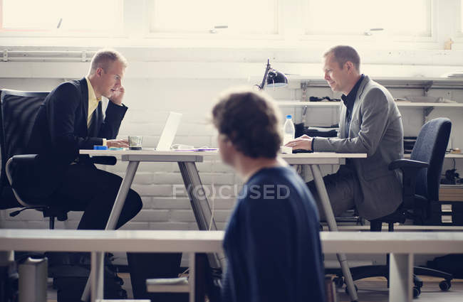 Businessmen sitting at table — Stock Photo