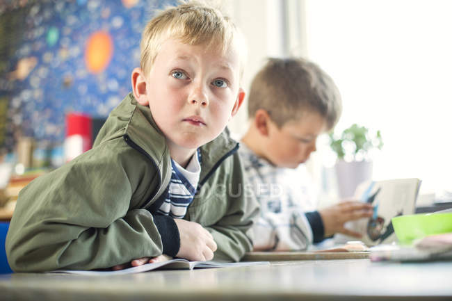 Cute boy sitting at table — Stock Photo