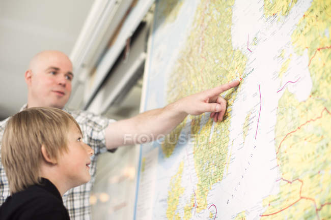 Low angle view of male teacher explaining map to boy in classroom — Stock Photo