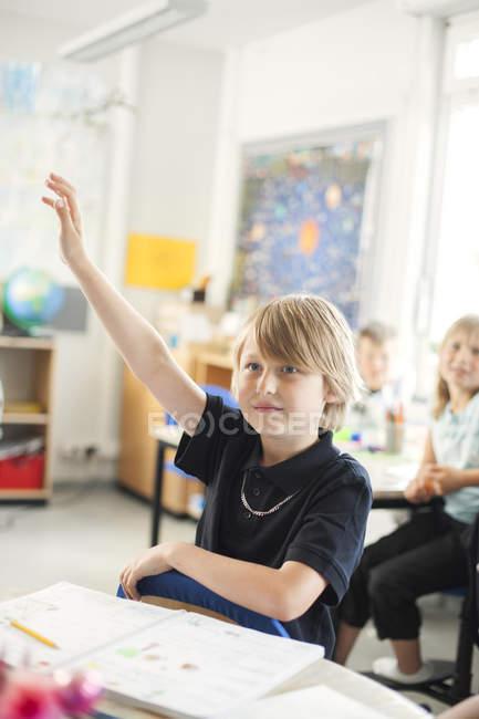 Écolier levant la main dans la salle de classe — Photo de stock