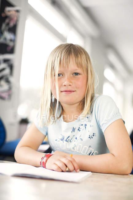Mignonne fille assise au bureau — Photo de stock