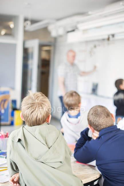 Bambini che esaminano insegnante — Foto stock