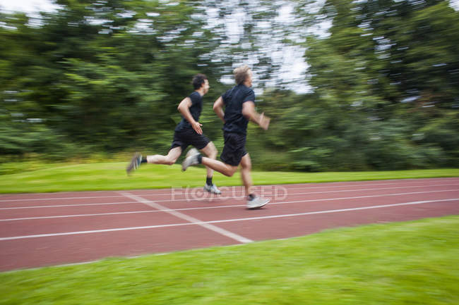Male athletes running on track — Stock Photo