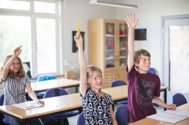 Étudiants hautes juniors élever les mains — Photo de stock