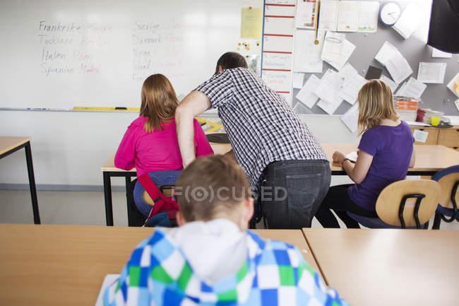 Écolière aide enseignant — Photo de stock