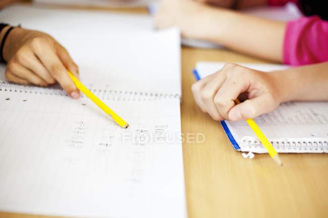Studenti in possesso di matita sopra i libri — Foto stock