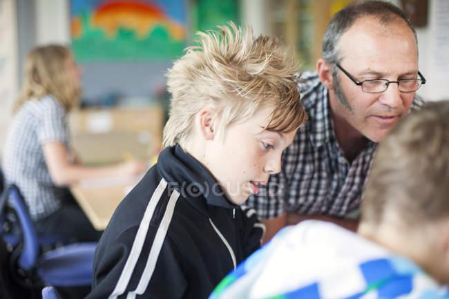 Insegnante che aiuta gli studenti junior high — Foto stock