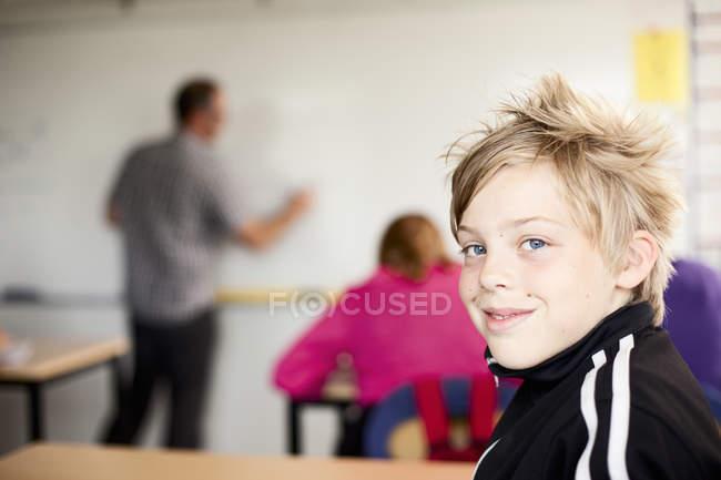 Portrait de jeune garçon assis dans la salle de classe — Photo de stock