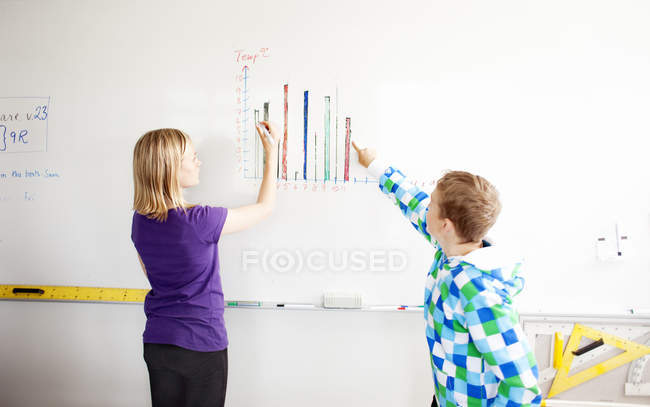 Boy and girl drawing chart — Stock Photo