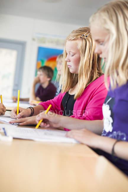 Écolières par écrit au bureau — Photo de stock