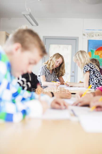 Étudiants qui étudient au pupitre dans la salle de classe — Photo de stock