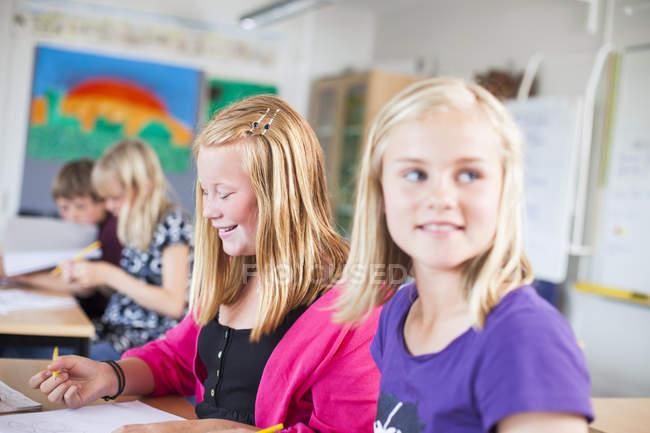 Joyeux écolières assis au bureau — Photo de stock