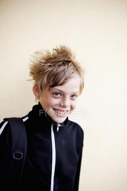 Счастливый мальчик у стены — стоковое фото