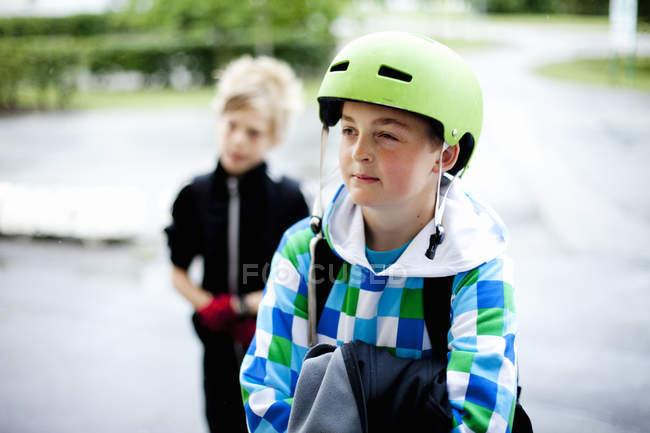 Port casque de garçon avec un ami — Photo de stock