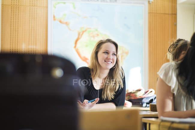 Heureuse lycéenne assise en classe — Photo de stock