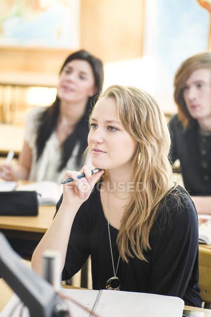 Les élèves du secondaire à l'écoute pour donner des conférences dans la salle de classe — Photo de stock