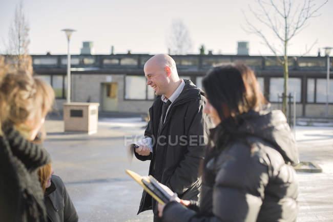 Усміхаючись вчитель розмовляти з учнів середніх шкіл на вулиці — стокове фото