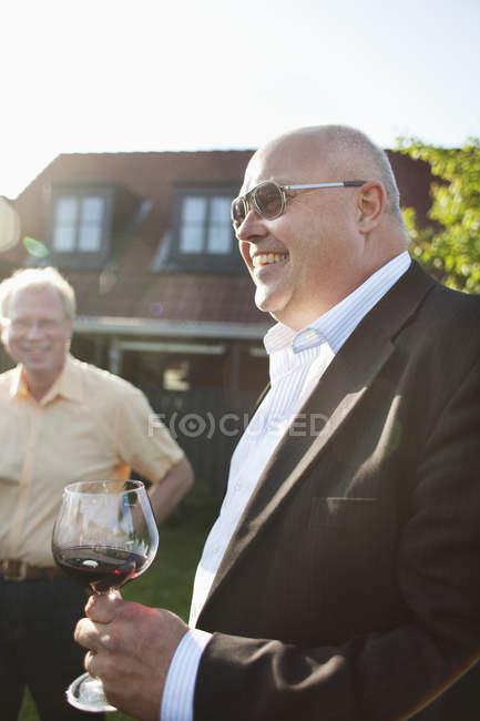 Мужчина держит бокалы на заднем дворе — стоковое фото