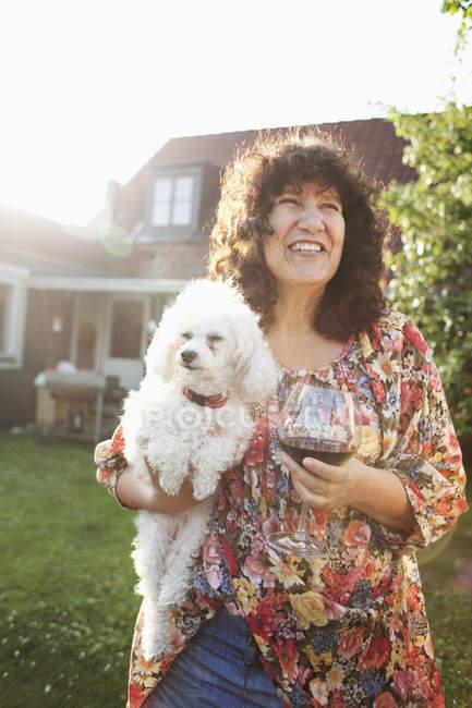 Женщина с красным вином и собакой — стоковое фото