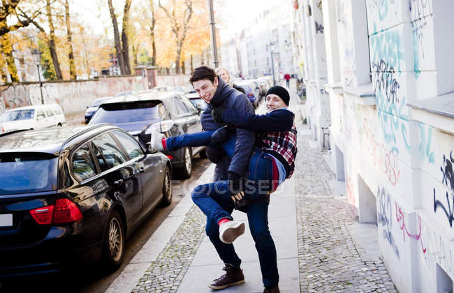 Man carrying male friend — Stock Photo
