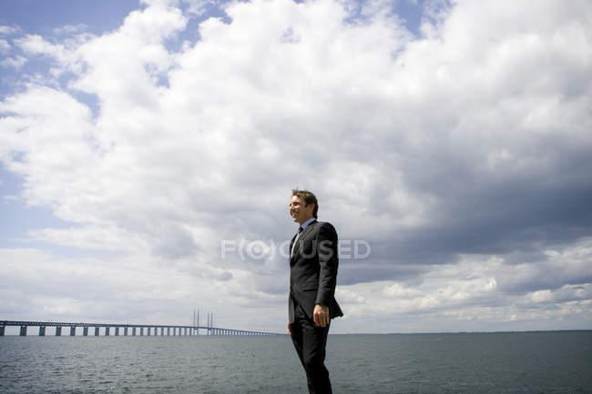 Перегляд бізнесмен в костюмі стояв на вітряний берегової лінії — стокове фото