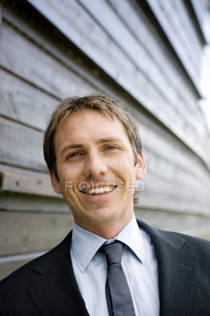 Porträt eines lächelnden Geschäftsmannes vor einer Holzwand — Stockfoto