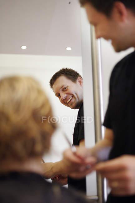 Primo piano del barbiere maschio sorridente che taglia i capelli irriconoscibili della persona al salone — Foto stock