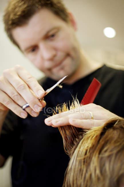 Vista de perto do homem cortando cabelo na barbearia — Fotografia de Stock