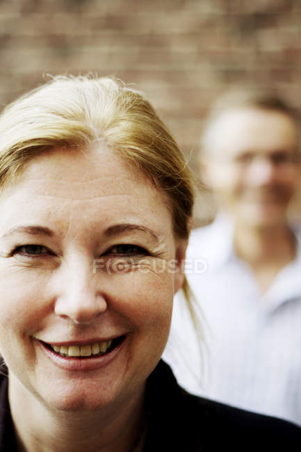 Close-up view of mature woman with man in background — Stock Photo