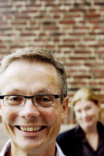 Ritratto ravvicinato di uomo sorridente con donna sullo sfondo — Foto stock