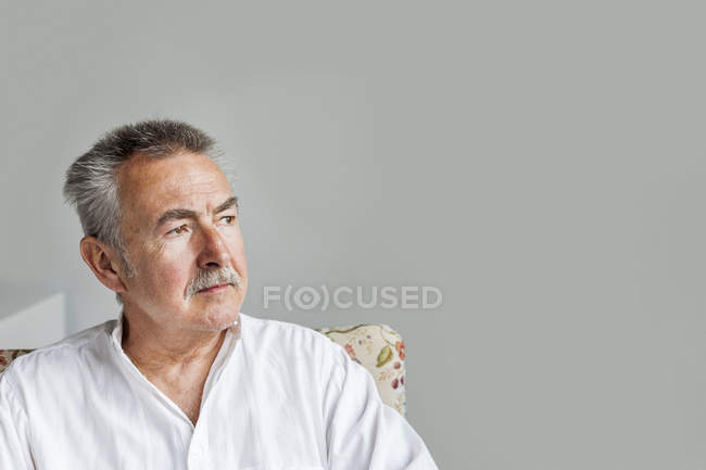 Senior man sitting against gray wall — Stock Photo