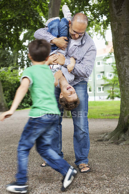 Playful father and sons — Stock Photo