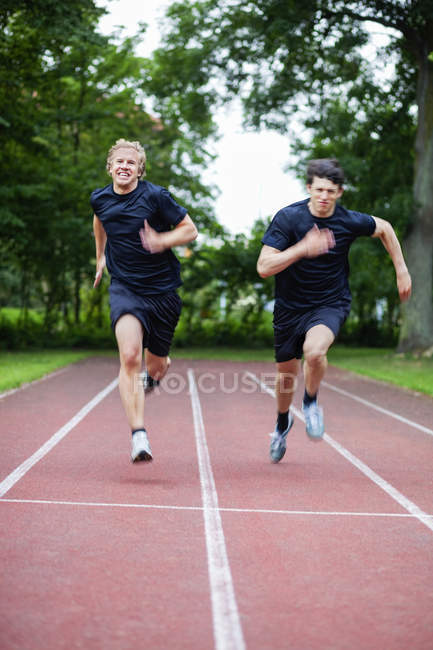 Young friends running on track — Stock Photo