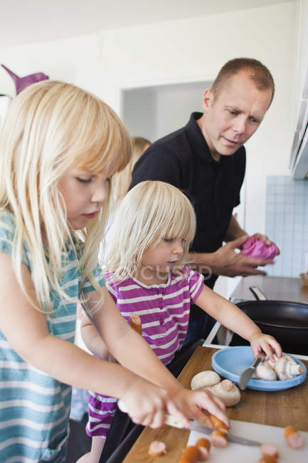 Daughter cutting sausages in kitchen — Stock Photo