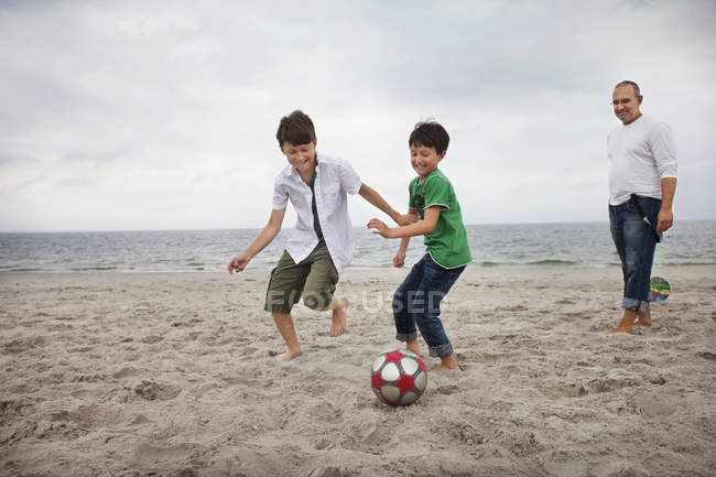 Sons playing soccer at beach — Stock Photo