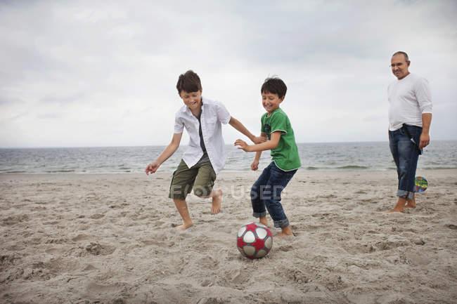 Söhne, die Fußball spielen, am Strand — Stockfoto