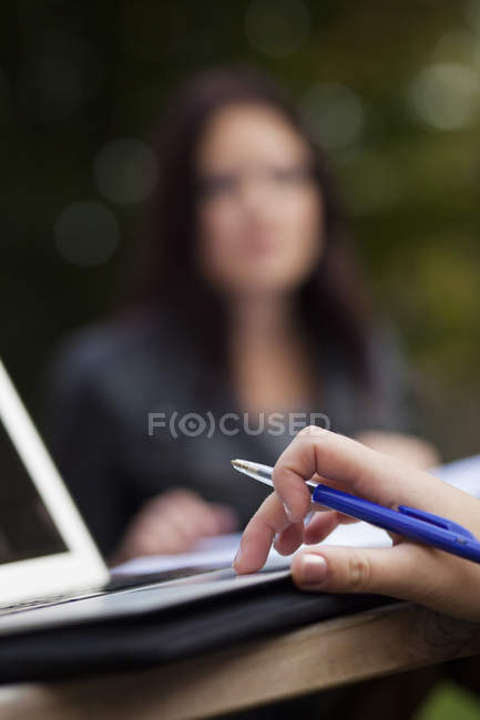 Woman with laptop with female friend — Stock Photo