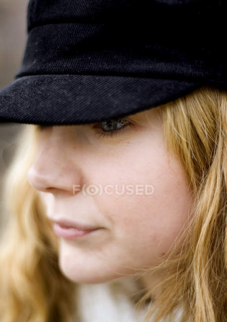 Portrait of thoughtful woman wearing black cap — Stock Photo