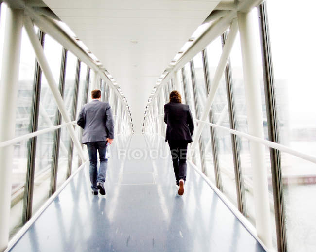 Бизнесмены, идущие по возвышенной дорожке — стоковое фото