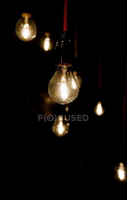 Glühbirnen über schwarz — Stockfoto