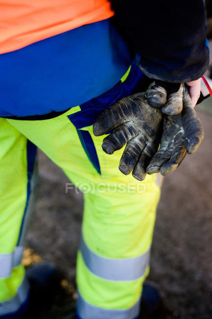 Construction worker holding messy gloves — Stock Photo