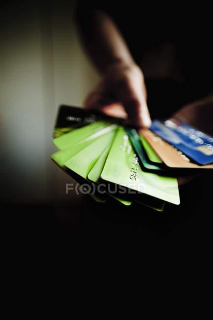 Manos sosteniendo varias tarjetas de crédito - foto de stock